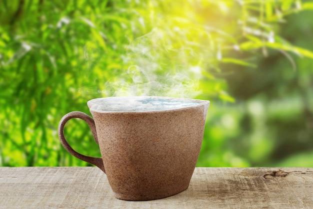 Heißer tasse kaffee auf hölzernem im garten.