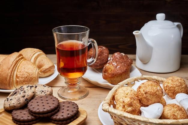 Heißer tee auf den tisch gestellt, frühstück am morgen getrunken, frühstück mit croissants und süßigkeiten auf holztisch
