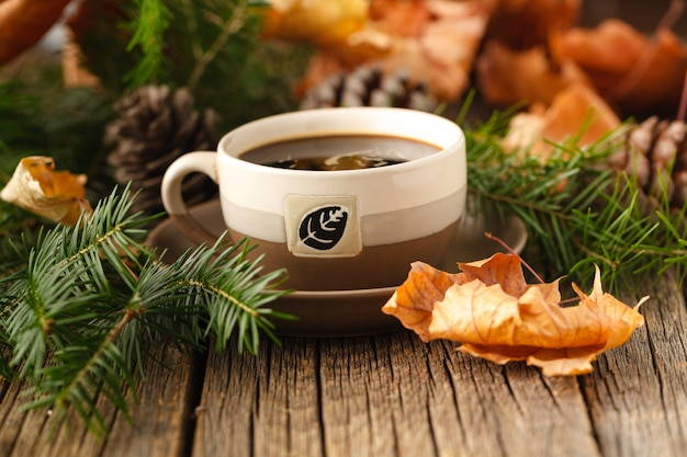 Heißer tee auf rustikalem holztisch mit waldelementen