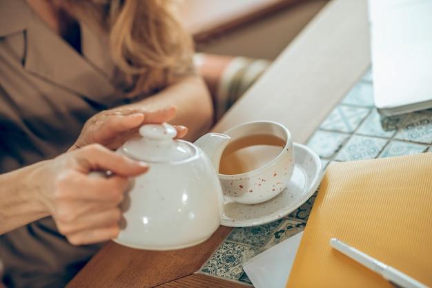 Heißer tee. frau gießt tee aus einer weißen teekanne in die tasse