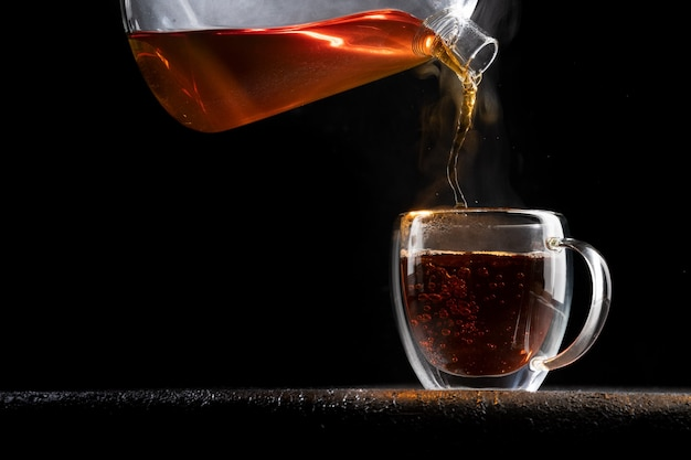 Heißer tee gießt in eine transparente tasse auf schwarzem hintergrund.