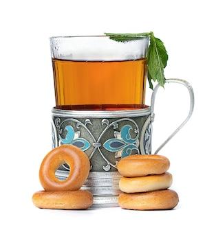 Heißer tee in einem glas und eine tasse mit bagels auf einem weißen raum