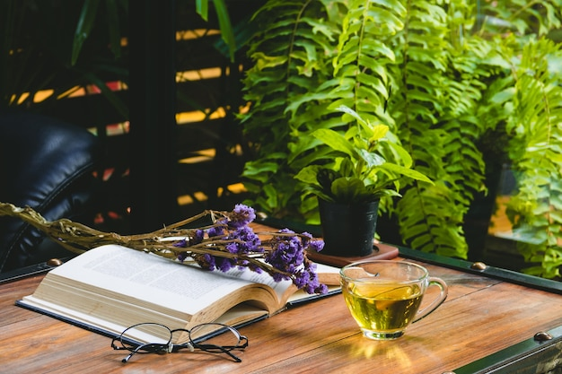Heißer tee in einer schale mit offenem buch und lesebrille mit trockenblume auf tabelle