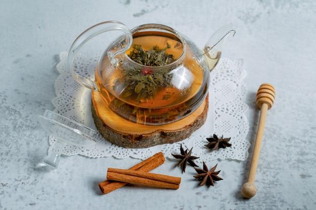 Heißer tee in teekanne mit honig und zimt.