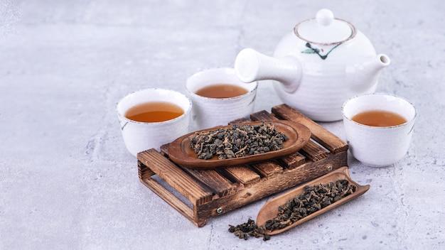 Heißer tee in weißer teekanne und tassen auf einem sieb über hellgrauem zementhintergrund, nahaufnahme, raumdesignkonzept kopieren.