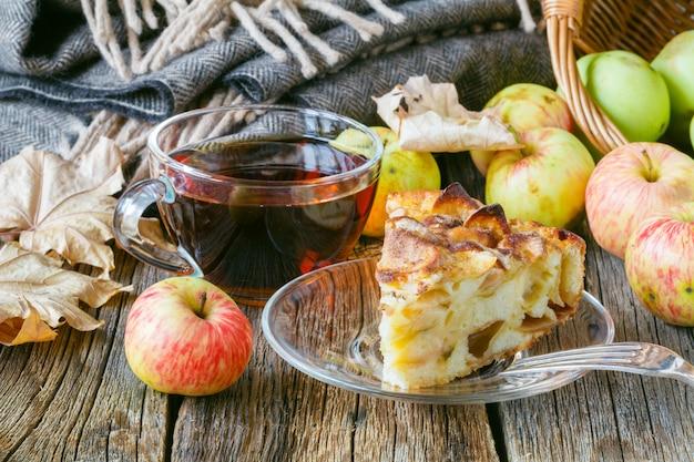 Heißer tee mit äpfeln und kuchen auf dem tisch