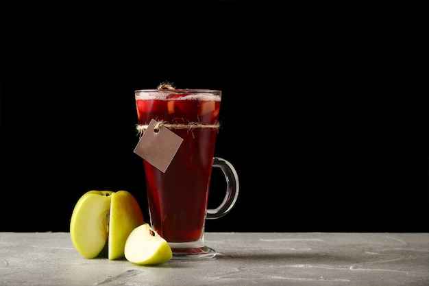 Heißer tee mit apfel in einem glühweinglas