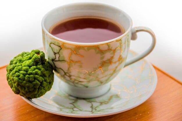 Heißer tee mit bergamotte auf holztisch in der kälte. winter.