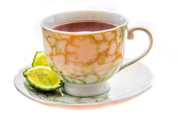 Heißer tee mit bergamotte auf weißem hintergrund in der kälte. winter.