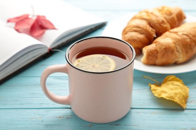 Heißer tee mit croissant und herbstlaub auf blau - saisonales entspannungskonzept. ansicht von oben