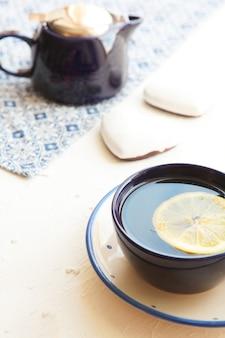 Heißer tee mit einer scheibe frischer zitrone bei blauer teetasse mit keksherzen teeset und blauer serviette