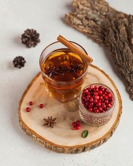 Heißer tee mit gewürzen, apfel und beeren in einem transparenten glasbecher auf einem holzständer. das konzept des wohnkomforts, herbst