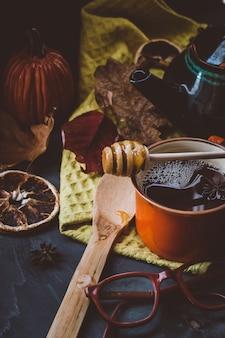 Heißer tee mit honig und zimt in einer orangefarbenen tasse herbstatmosphäre auf einer dunklen oberfläche