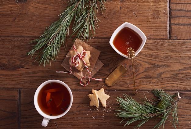 Heißer tee mit honig und zitrone neben lebkuchen