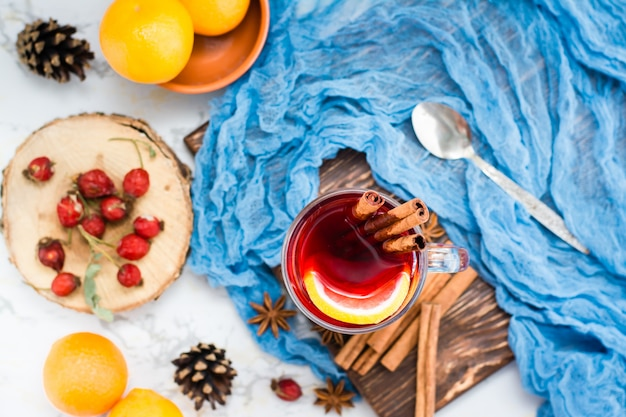 Heißer tee mit zitrone und zimt in einem glas. winterwärmegetränk. draufsicht