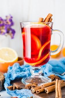 Heißer tee mit zitrone und zimt in einem glas. winterwärmegetränk