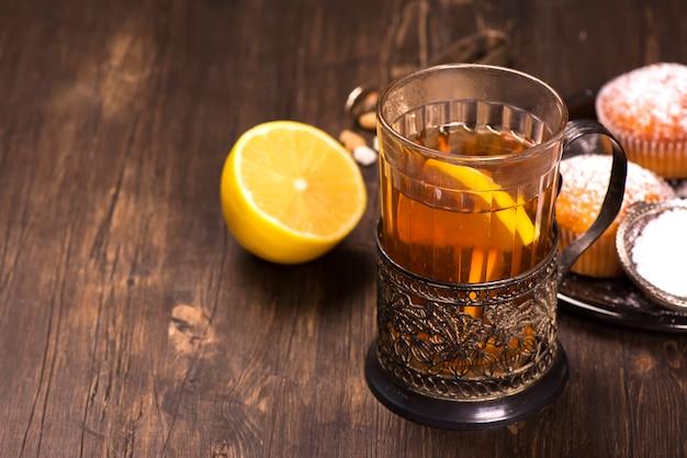 Heißer tee mit zitronenscheiben in einer alten glasschale mit weinleseglashalter