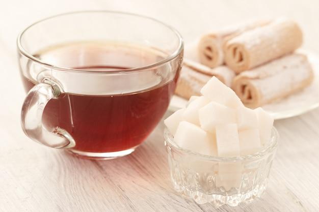 Heißer tee mit zuckerwürfeln und -bonbons auf tabelle