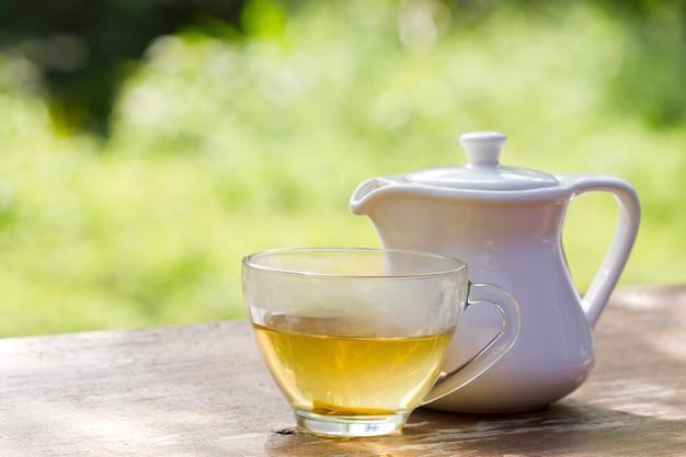 Heißer tee oder eine tasse tee und weiße teeschüssel auf holztisch mit raum für erfrischungen