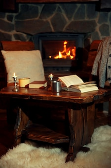 Heißer tee oder kaffee in tasse, buch und kerzen auf vintage-holztisch. kamin als hintergrund