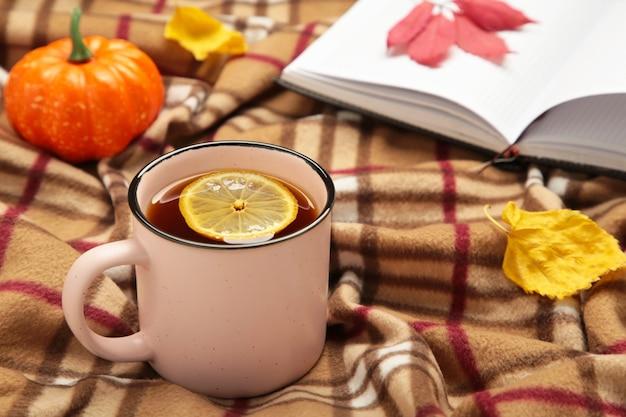 Heißer tee und herbstblätter mit notizbuch auf plaid - saisonales entspannungskonzept. gemütliches konzept