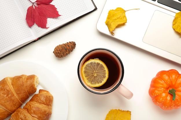 Heißer tee und herbstblätter mit notizbuch auf weiß - saisonales entspannungskonzept. ansicht von oben