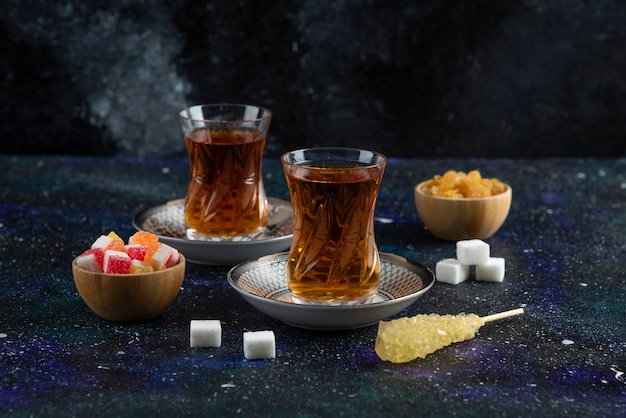 Heißer tee und süßigkeiten auf blauer oberfläche