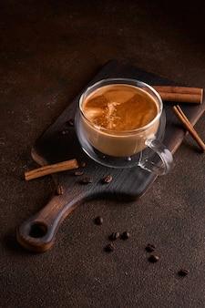 Heißer und aromatischer kaffee, der aus der glastasse auf dunklem hintergrund verschüttet wird. konzept des leckeren erfrischungsgetränks mit kaffee. kopieren sie platz für text, menü oder rezept