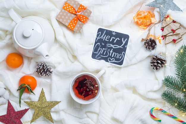 Heißer weihnachtstee mit zuckerstange gegen dekorationen, geschenkboxen, band und mandarine