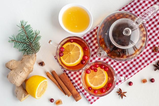 Heißer wintertee zur stärkung des immunsystems. zwei tassen und ein glaskessel mit tee, zitrone, ingwer und preiselbeeren