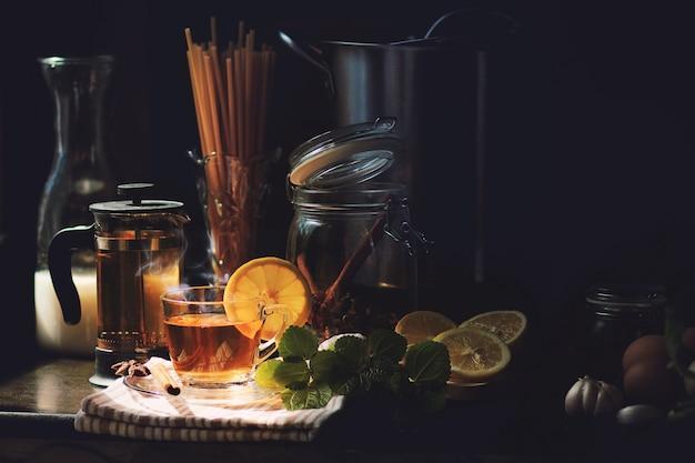 Heißer zitronenkräutertee mit dampf und dampf in der küche. morgenlicht erstrahlt auf der kücheninsel mit teetasse, nudeln, milch, schmortopf und kräutern. konzept des glücklichen momentes mit tee.
