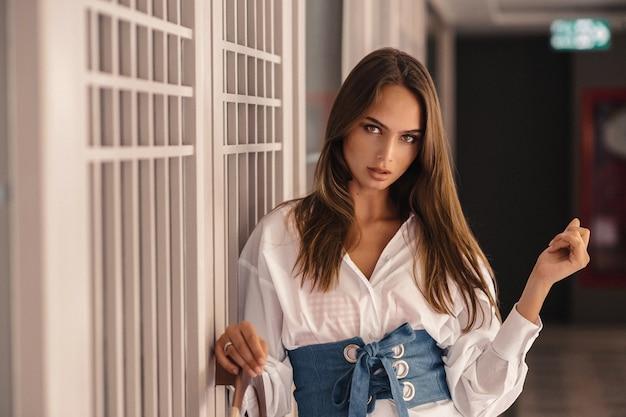Heißes brunettemodell, das in einem weißen hemd mit denimgürtel aufwirft. außen.