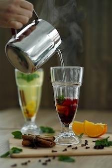 Heißes dampfendes wasser vom stahltopf im glas mit vitamingetränk gießen. winter heiße saisonale getränke