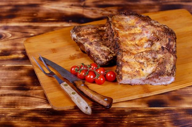 Heißes fleisch richtet schweinefleischrippen mit tomaten auf einem alten rustikalen brett an