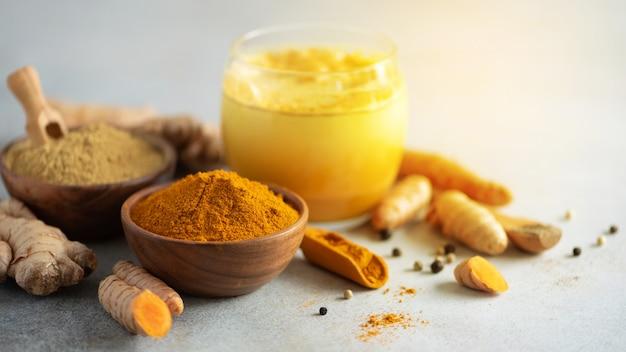 Heißes gesundes getränk. gelbwurzlatte, goldene milch mit gelbwurzwurzel, ingwerpulver, schwarzer pfeffer über grauem hintergrund.