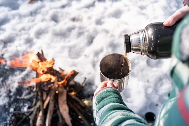 Heißes getränk aus der thermoskanne auf einem campingplatz einschenken. person, die nahe einem lagerfeuer, gesichtspunktschuß warm erhält