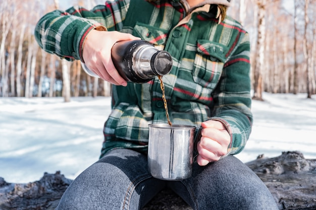 Heißes getränk aus der thermoskanne auf einem campingplatz einschenken. person in einem winterwald während einer wanderung, die warm erhält