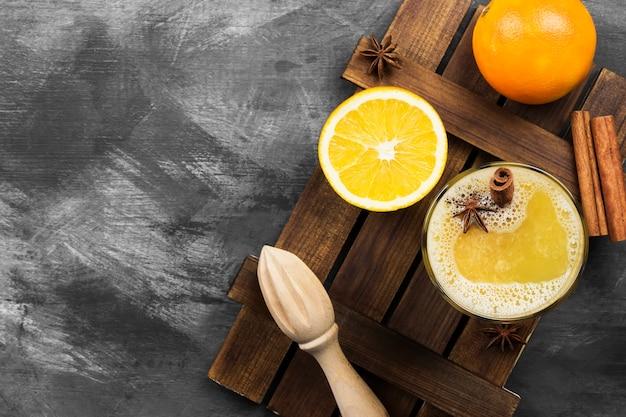 Heißes getränk des winters von den orangen und von den gewürzen auf einer schwarzen oberfläche