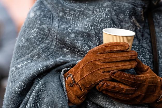 Heißes getränk in pappbecher in händen mit handschuhen