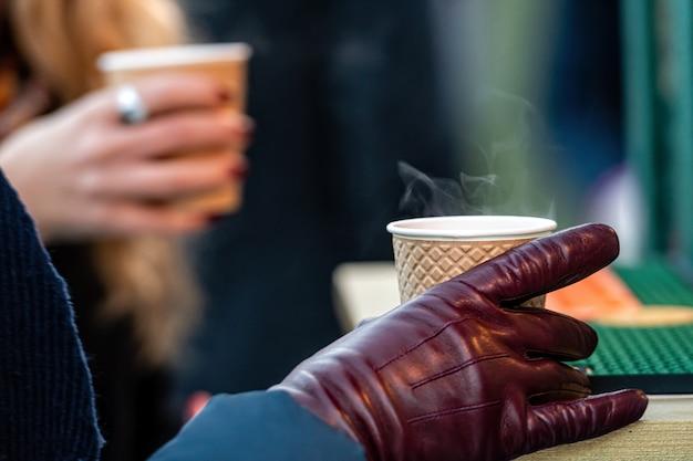 Heißes getränk in pappbechern für getränke zum mitnehmen (tee oder kaffee) in händen mit handschuhen, nahaufnahme