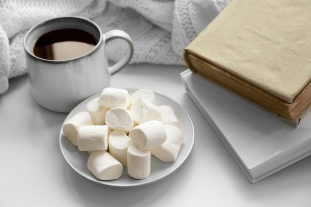 Heißes getränk mit büchern und marshmallows auf der fensterbank