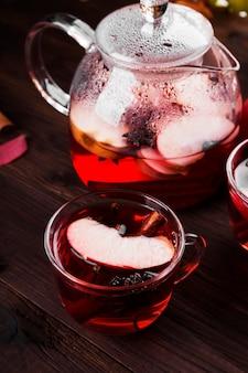 Heißes getränk mit rotem tee des hibiskus mit apfel, zimt und anis in der glasteekanne und in zwei gläsern