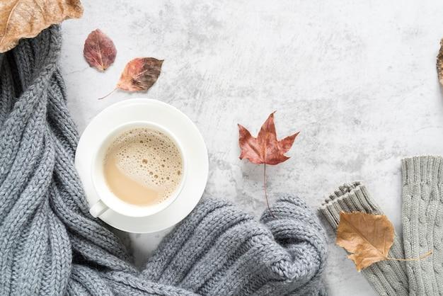 Heißes getränk mit warmer strickjacke auf heller oberfläche