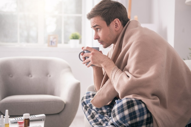 Heisses getränk. netter junger mann, der eine tasse heißen tee trinkt, während er krank ist