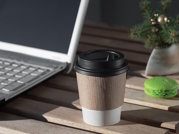Heißes getränk, tee oder kaffee in einem pappbecher auf einem holztisch neben dem laptop. auf dem tisch liegen makronen