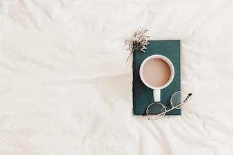 Heißes Getränk, Brillen und Kraut, die auf Buch auf Bettlaken liegen