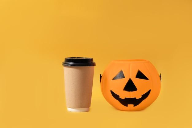Heißes herbstgetränk zum mitnehmen mock-up-tasse halloween kaffee zum mitnehmen kürbis isolierten gelben text oder logo