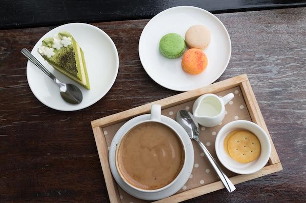 Heißes kaffeefrühstücksset mit kuchen des grünen tees und frischer makrone im gemütlichen café im freien