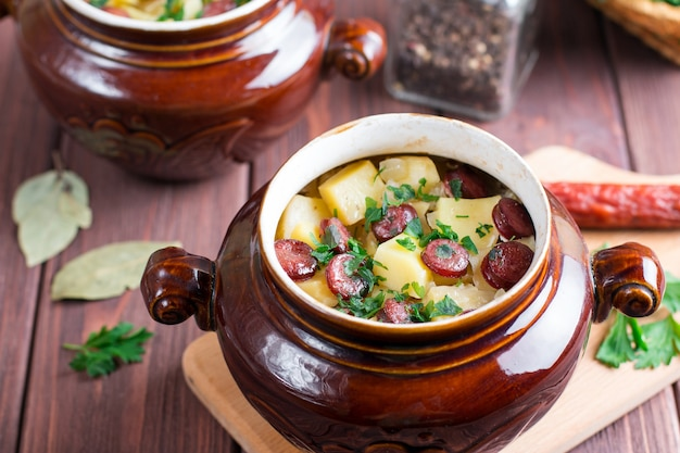 Heißes kartoffelgulasch mit speck und würstchen in einer keramikschale