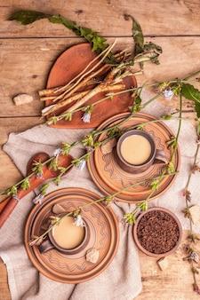 Heißes koffeinfreies natürliches chicorée-getränk in keramikbechern auf einem holztisch. gesunder alternativer ersatz für kaffee, koffein. blaue zichorienblüten, frische wurzeln, draufsicht